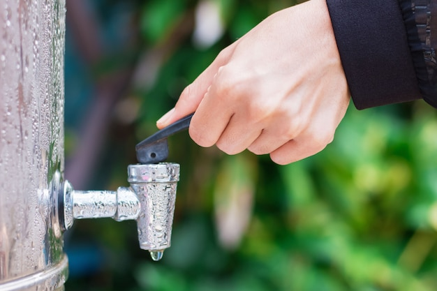 The woman's hand is about to open stainless steel dispenser cooler valve