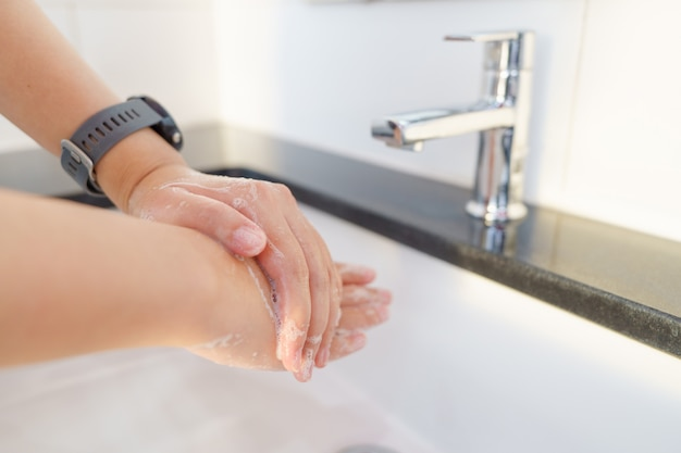 The woman's hand is going to open the faucet to wash hands.