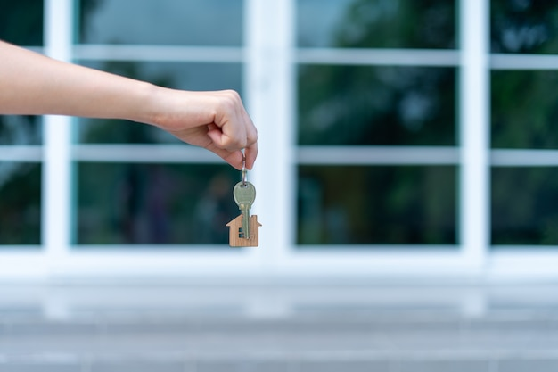 A woman's hand is handing over a key with a key ring house in the background of a modern house.