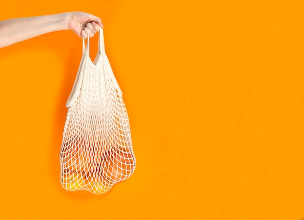 Woman's hand is on hold string bag with oranges and grapefruits on orange background.