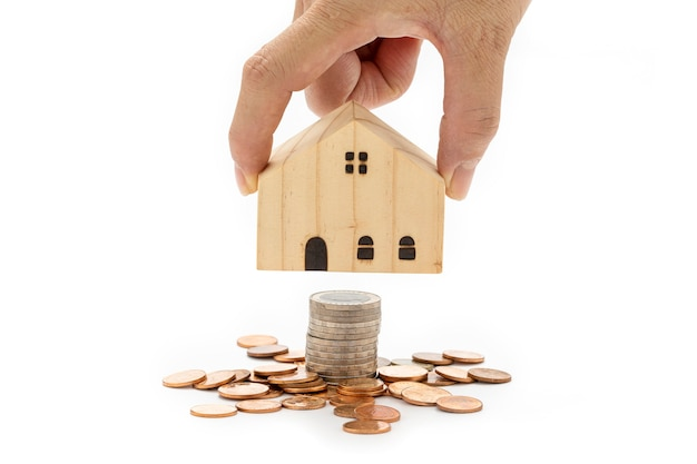A woman's hand is holding a model wooden house on stack of coins on white background.