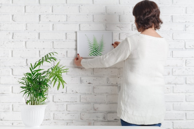 Woman's hand is holding photo frame and concrete pot with home plant