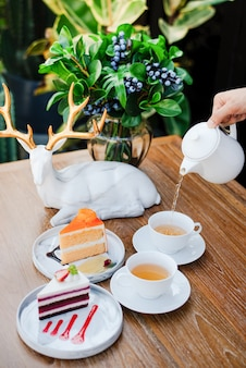 The woman's hand is pouring hot tea in the morning and cakes.