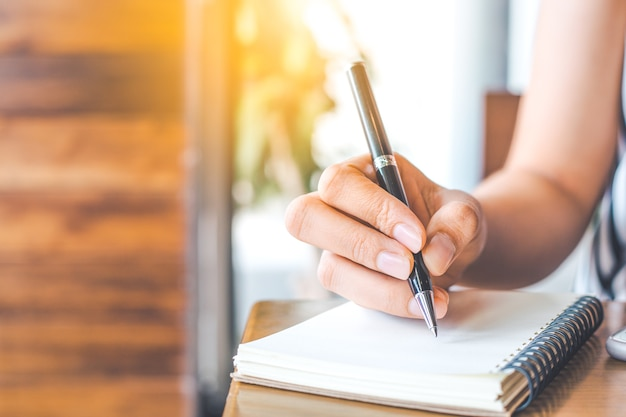 Woman's hand is writing on a blank notepad with a pen on a wooden desk.