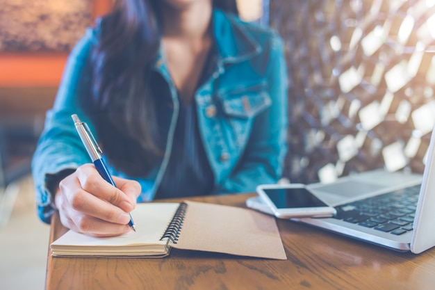 A woman's hand is writing on a notepad with a pen and a phone with a laptop.