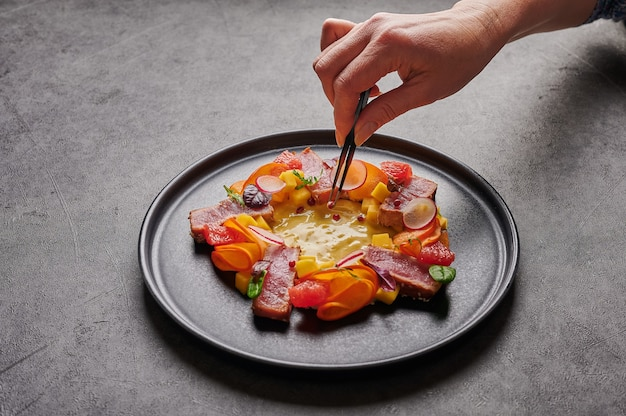 Woman's hand lays out the grain of red pepper with tweezers to homemade salad with tuna steak, mango sauce, herbs and spices on a dark plate, close up, food decorating concept