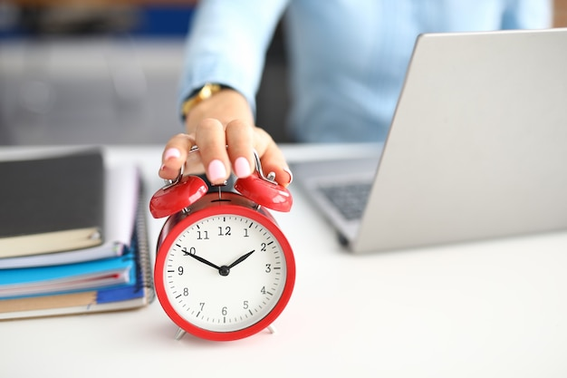 Woman's hand lies on red alarm clock notebooks and laptop lie next to it