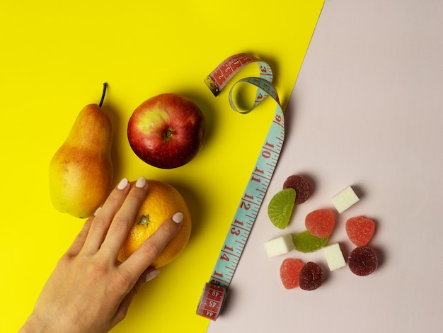 A woman's hand makes a choice in favor of proper nutrition. on pink and yellow background useful fruits, apple pear orange and harmful sweets are laid out. in the middle is a measuring tape