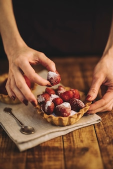 Woman's hand making strawberries tart on wooden table