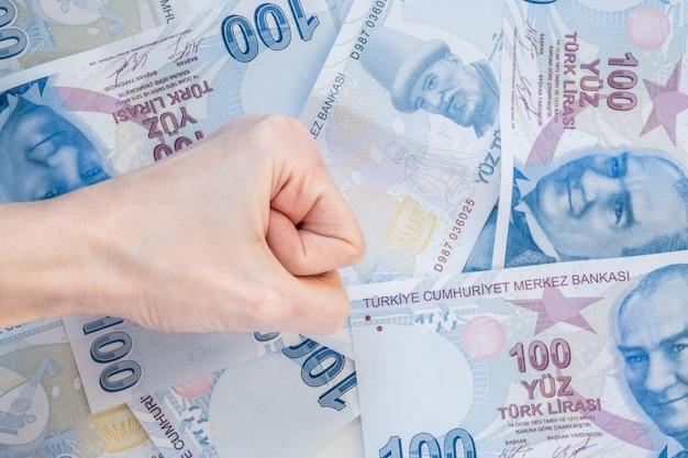 100 터키 리라 지폐의 무리에 여자의 손