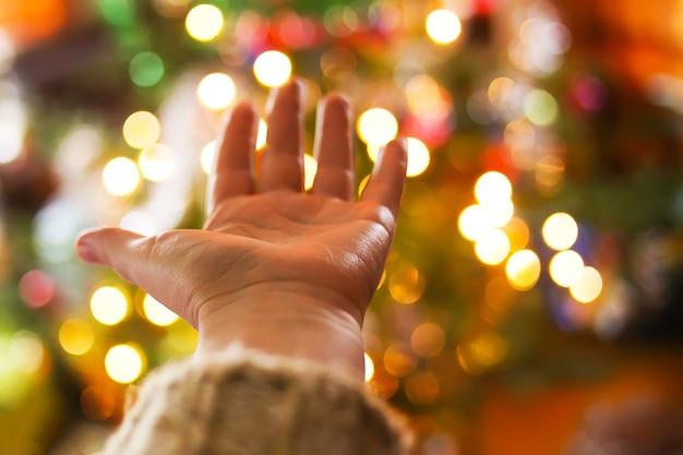 시골집 내부에 장식된 크리스마스 트리의 defocused 밝은 ligths에 여자의 손. 흐리게 새 해 축제 배경입니다.