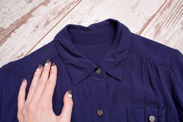 青いシャツの襟に女性の手