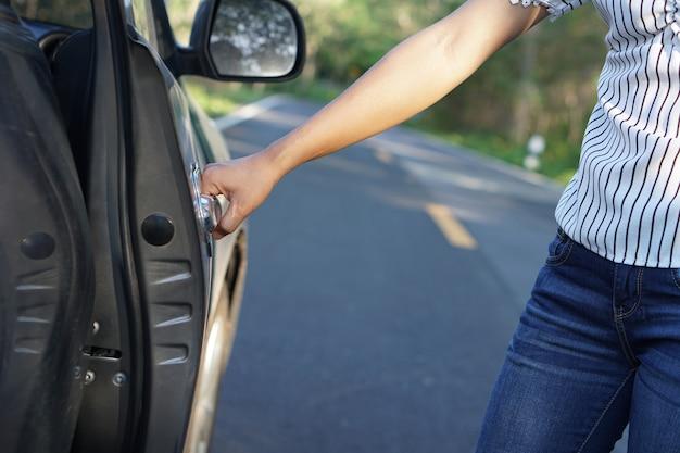 여자의 손은 자동차의 문을 엽니 다.
