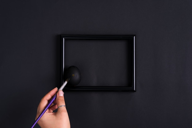 Woman's hand paints easter egg by paintbrash in black color on the same color photo frame and background.