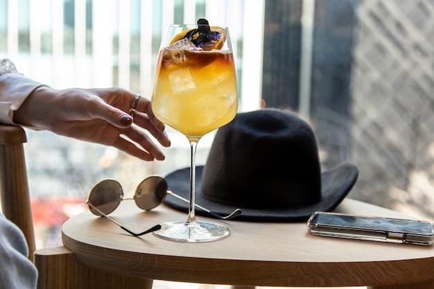 Женская рука выбирает бокал для вина, наполненный вкусным натуральным ликером из травяного чая