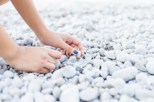 Woman's hand picking up pebbles at beach