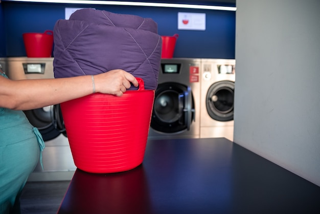 Woman's hand placing clothes in a laundry basket in a laundromat.