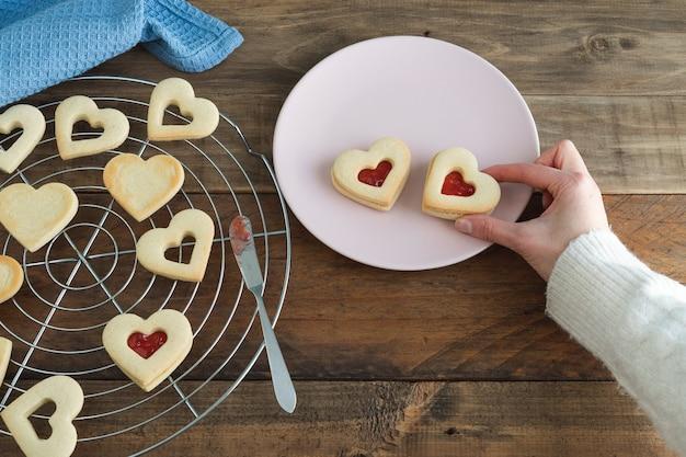 Женская рука помещает печенье в форме сердца на тарелку. скопируйте пространство. концепция дня святого валентина.