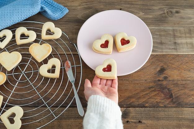 Женская рука помещает печенье в форме сердца на тарелку. концепция дня святого валентина.