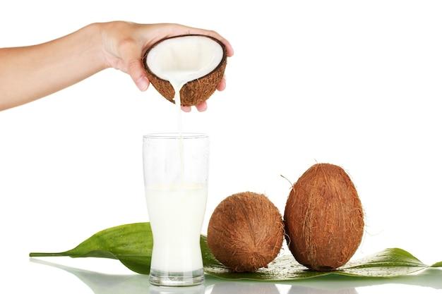 Женская рука наливает кокосовое молоко в стакан на белом