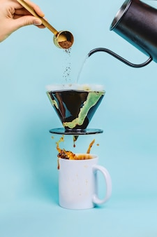 Woman's hand pouring coffee grounds into levitating ceramic dripper above the white cup with splashing coffee, alternative brewing concept, selective focus