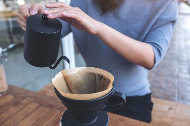 빈티지 나무 테이블에 드립 커피를 만들기 위해 뜨거운 물을 붓는 여자의 손