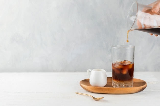 Woman's hand pouring iced coffee in a tall glass on a wooden tray, selective focus, copyspace