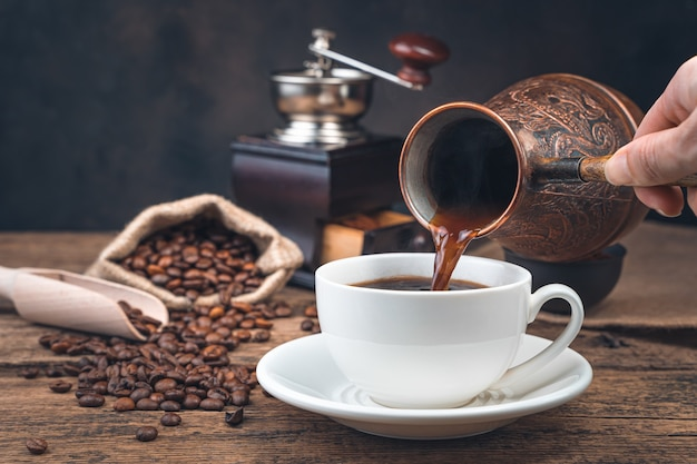 A woman's hand pours coffee into a mug of turki on the wall of a coffee grinder and coffee beans. side view, copy space. tinted image.