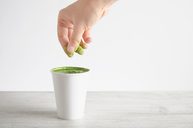 Woman's hand pours green organic premium matcha powder on top matcha latte in take away paper glass isolated on wooden table, white background