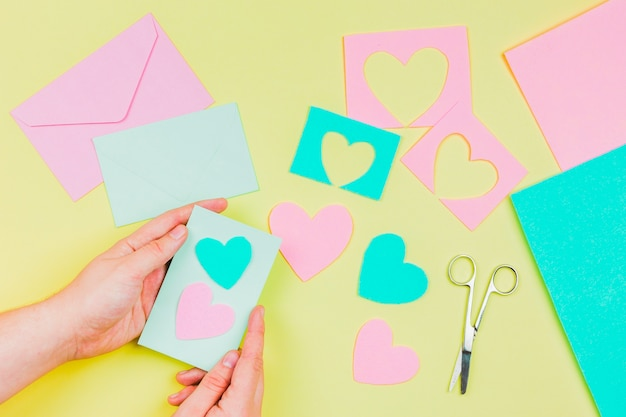 Woman's hand preparing heart shape greeting card on yellow background
