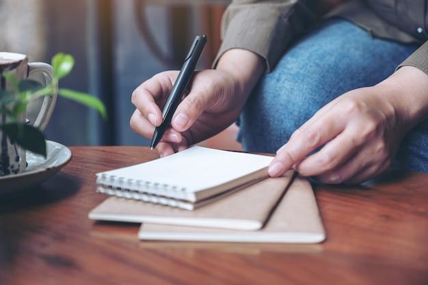 나무 테이블에 커피 컵과 빈 노트북에 쓰기를 준비하는 여자의 손