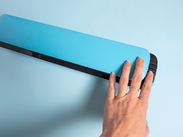 A woman's hand presses the button of a blue vacuum packer. the concept of preserving products.