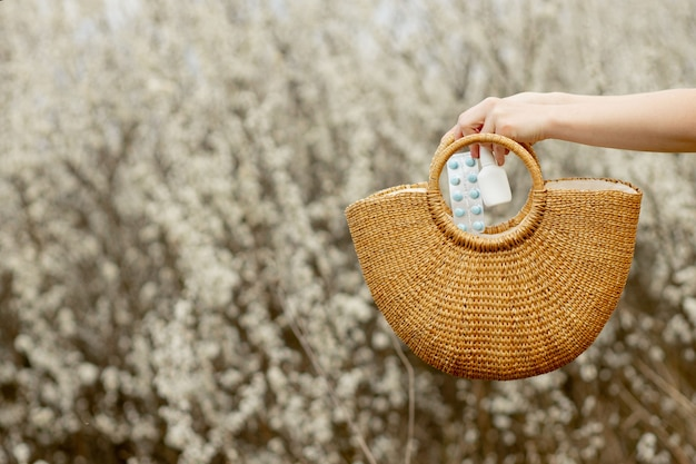 Женская рука кладет таблетки от аллергии в сумку на цветущем фоне