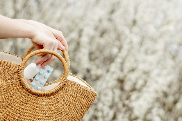 여자의 손은 개화에 가방에 알레르기 약을 넣습니다.