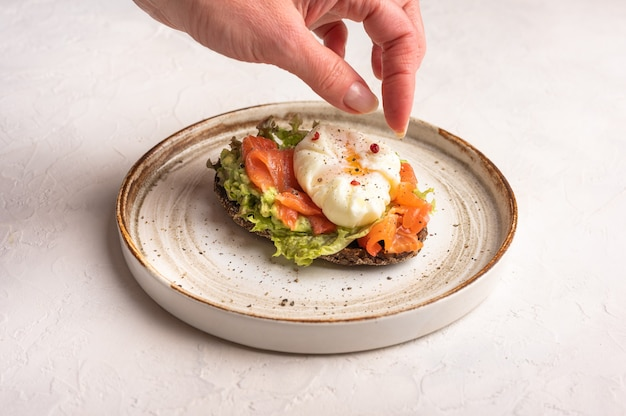 Woman's hand puts pepper on poached egg toast with avocado, salted salmon, arugula and rye bread on a ceramic plate, close up. healthy food concept