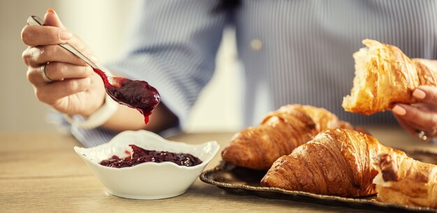 Woman's hand puts spoon of jam on a croissant having a breakfast.