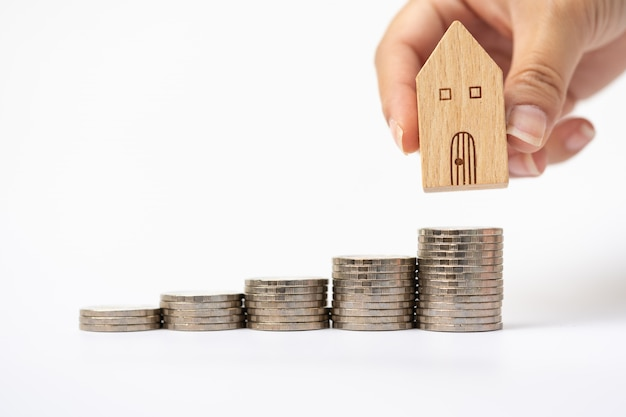Woman's hand putting house model on coins stack.