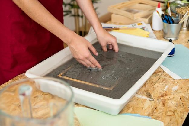 La mano della donna che mette la muffa in pasta di carta