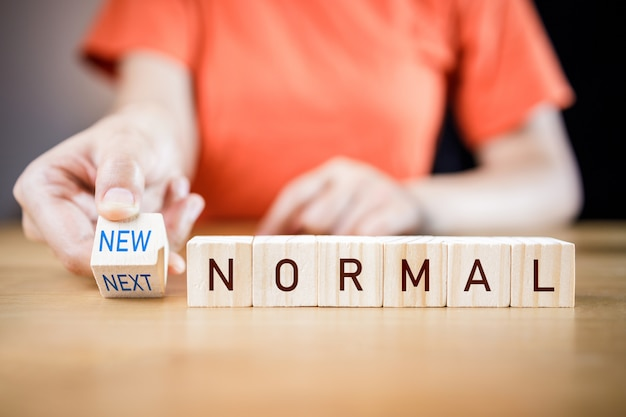 Woman's hand putting wooden cubes with concept new or next normal.