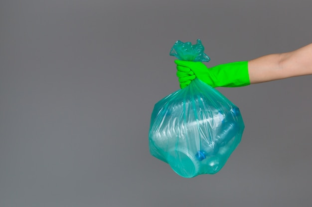 A woman's hand in a rubber glove holds a transparent green garbage bag