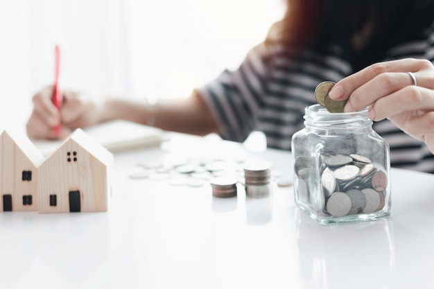 Woman's hand saving a coin into the glass jar for planning, housing and property financial concept