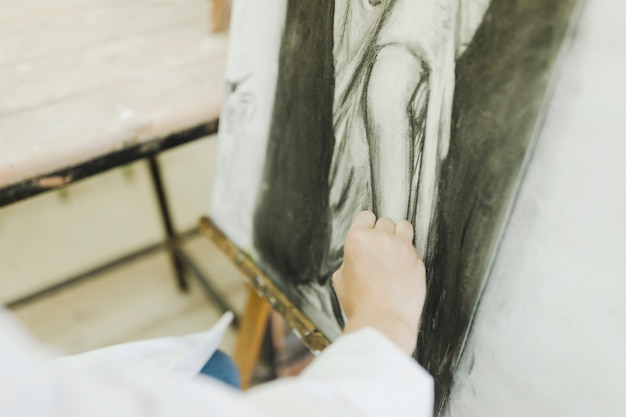Woman's hand sketching female on canvas