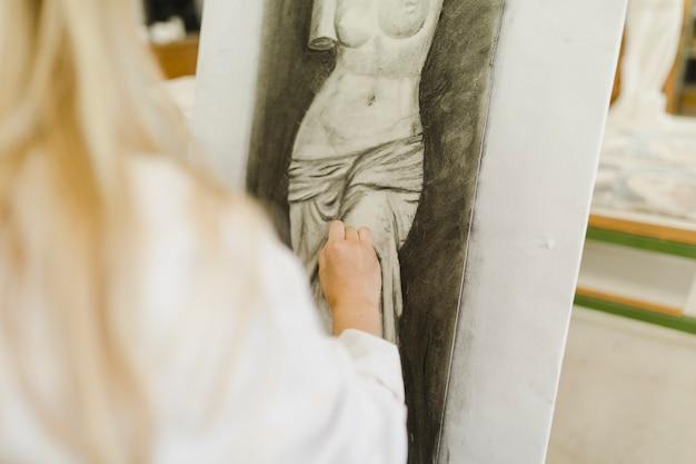 キャンバスに彫刻をスケッチする女性の手