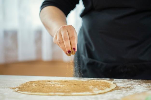 Woman's hand sprinkles cinnamon over the dough