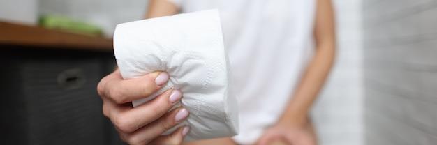 女性の手がトイレのクローズアップでトイレットペーパーのロールを絞ります。排便時の痛み肛門科の概念。
