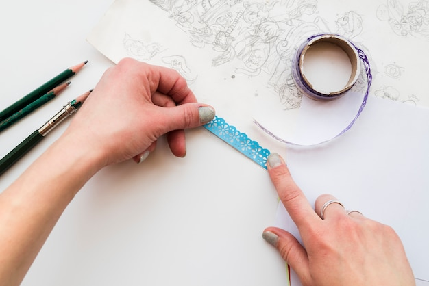 Woman's hand sticking the blue lace on drawing paper over the white backdrop