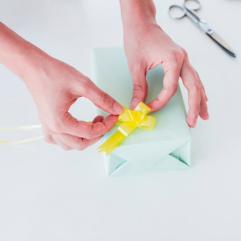 Woman's hand sticking the yellow ribbon on wrapped gift box over white desk