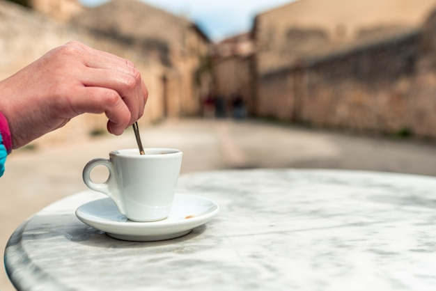 바 테라스에서 커피를 저어 여자의 손
