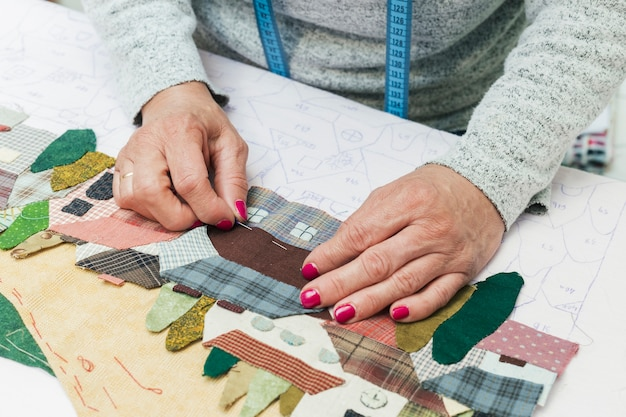 Woman's hand stitching fabric house with needle at workplace