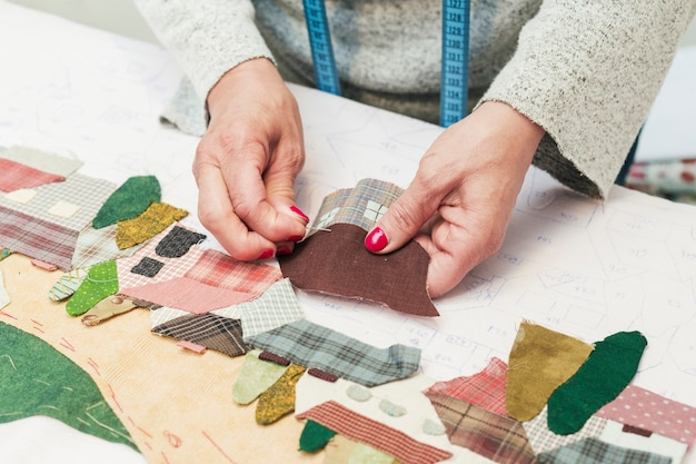 Woman's hand stitching fabric patch house with needle at workplace